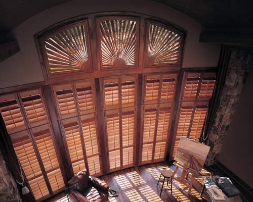 brown shutters on tall windows